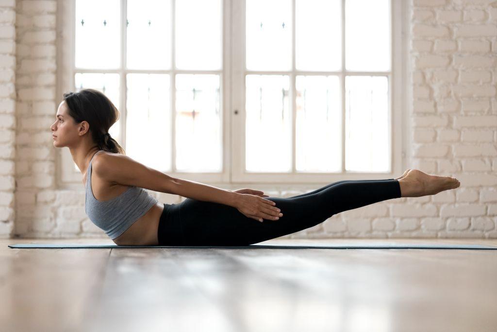 zena pokazuje kako se radi joga poza skakavac